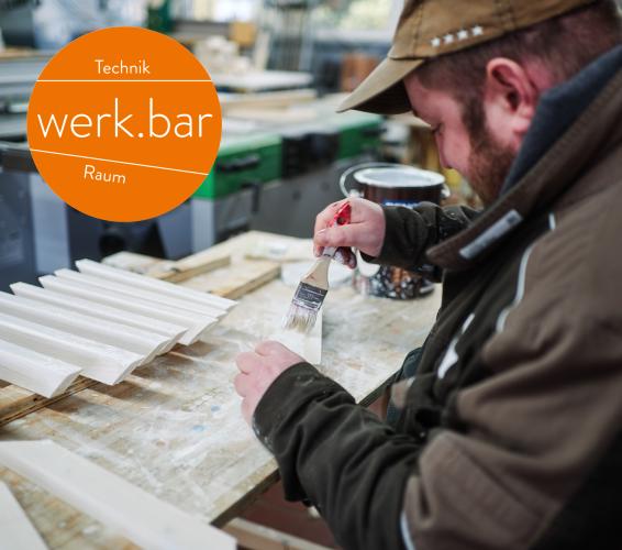 Holz. Technikraum. Werkbar. Person in einer Werkstatt streicht Holzlatten mit einem Pinsel.