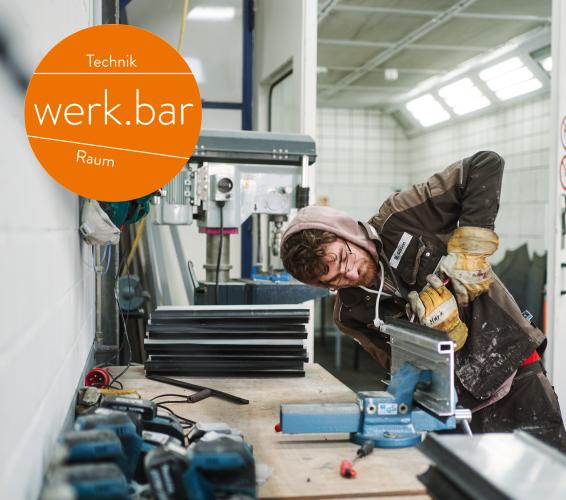 Metall. Technikraum. Werkbar. Person steht an einer Werkbank und bearbeitet ein Stück Metall im Schraubstock.