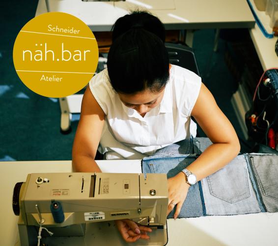 Schneider Atelier. Nähbar. Person sitzt an einer Nähmaschine und näht ein Stück Jeansstoff.