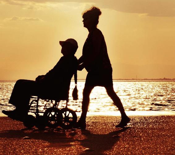 Umgang mit nicht-behinderten MEnschen: PErson in Rollstuhl und PErson die schiebt