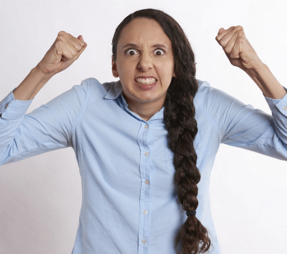 Umgang mit Kritik: Frau mit zusammengemissenen Zähnen  und geballten Fäusten